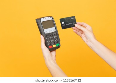 Close up cropped photo of female holding in hands wireless modern bank payment terminal to process acquire credit card payments, black card isolated on yellow background. Copy space for advertising