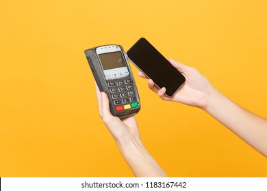 Close up cropped photo female holding in hands wireless modern bank payment terminal to process and acquire credit card payments mobile phone isolated on yellow background. Copy space for advertising