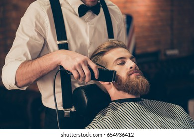 Close up cropped photo of a hairdresser`s work for a handsome young guy at the barber shop. He is doing styling with the electric shaver for his red beard