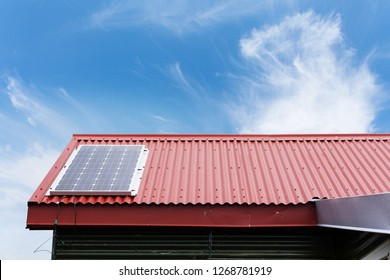 Close up cropped photo of little house with red rivets roof and small solar panel install on top against peaceful blue sky