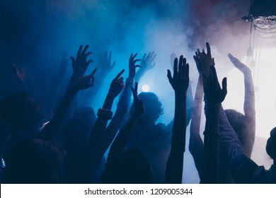 Close up cropped photo of people raised hands up in blue whire smoke having fun, dancing in the darkness on city club background
