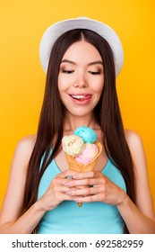 Close up cropped photo of tasty ice cream of three scoops of different flavors, young asian girl is holding it, has a tongue out, so hungry and cheerful