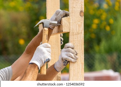 Close up cropped photo of two workers in white protective gloves holding plank board installing it on special house hold construction using hammer and nails