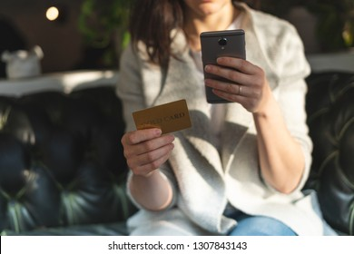 Close up cropped photo of unrecognizable lady in trend, trendy clothes inside loft interior space in restaurant. She sitting in chair holding plastic card and portable telephone equipment