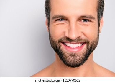 Close up cropped portrait with copy space of cheerful, joyful, virile, manly, attractive, naked, unshaven, handsome, stunning man with ideal, perfect face skin, looking at camera over gray background
