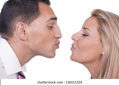 Close cropped portrait of the faces of a young man and woman preparing to kiss leaning towards each other with their lips puckered, isolated on white