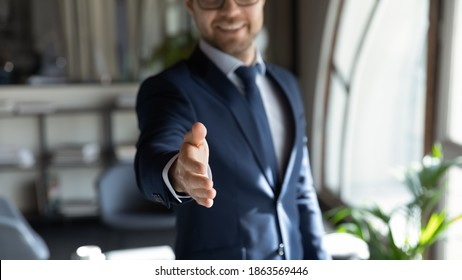 Close up cropped portrait of smiling successful friendly young man in formal attire hr recruiter stretching hand to camera glad to offer you job in company, greeting spectator as new workforce member