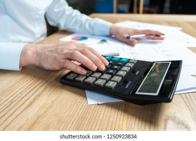 Close up cropped sale manager agent or analysis marketer accounting assistant  lady in her formal wear she sit behind table in bright loft interior count investments on calculator focus on hand