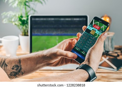 Close up cropped shot of male hands making bets using gambling mobile application on his phone. Man watching football match online broadcast on his laptop waiting for winning results.