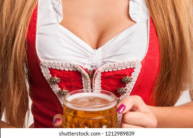 Close up cropped shot of a sexy Bavarian woman wearing dirndl holding mug of beer, posing seductively. Big breasted Oktoberfest waitress with perfect shapely body serving beer