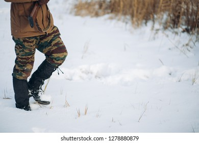 close up cropped sside view photo. man with a gun is walking on a snowy field. copy space. guy is spending time in the winter forest