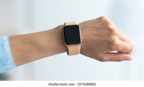 Close up cropped view of female hand with smart watch with black blank screen, selective focus, blurred background. Smartwatch - modern digital gadget with empty display, copy space
