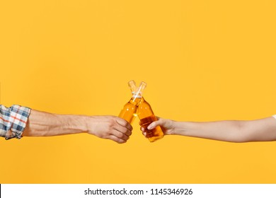 Close up cropped of woman and man two hands horizontal holding lager beer glass bottles and clinking isolated on yellow background. Sport fans cheer up. Friends leisure lifestyle concept. Copy space