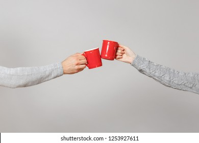 Close up cropped of woman, man two hands horizontal holding red cups of tea, clinking isolated on grey wall background. Friends leisure, healthy lifestyle, ill cold season concept. Mock up copy space