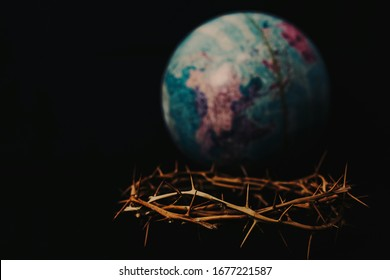 Close up of crown of thorns of Jesus over blurred world globe on black background can be used for Christian concept , Easter concept with copy space