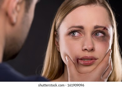 Close up of crying scared female face with bruise. Man holding woman face aggressively