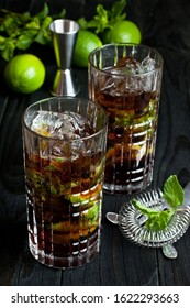 Close up of Cuba libre  cocktail with cola, rum,  ice and mint in glass  on dark background