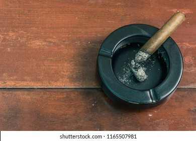 close up of a Cuban cigar and a black ceramic ashtray on the wooden table
