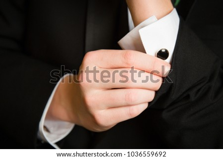 Close up of cufflinks being put on by teenage boy getting ready for prom.
