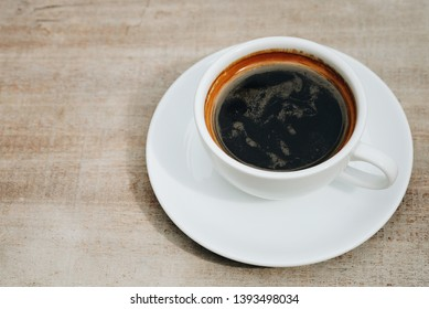 Close up cup of americano coffee on wooden table background