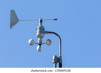 Close up of a cup anemometer on a pole in a small German port. The device measures the wind speed and the wind direction. During the day with sunshine and blue sky.
