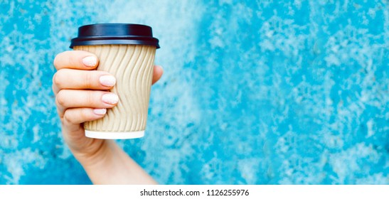 Close up of Cup of cappuccino in female hand on blue wall background. Place for text, banner.