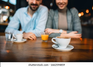 close up of cup of coffee, blurred couple in background