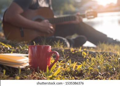 Close up cup of coffee. Man playing guitar, sitting on grass.