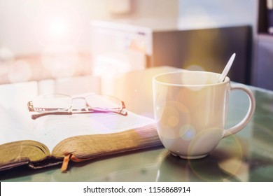 close up of a cup of coffee with open bible and eye glasses  for morning devotion on office table with window light and bokeh effected