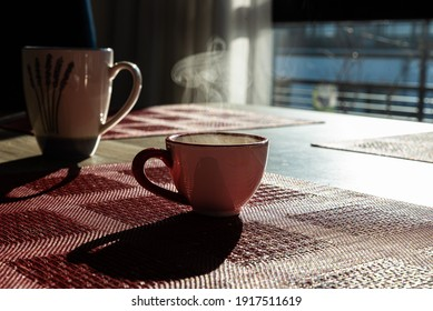 Close up of a cup of coffee with sunlight on a red placemat