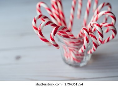 Close up of a cup full of candy canes on white weathered wood table.