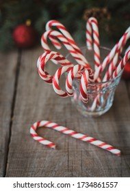 Close up of a cup full of candy canes against Christmas backdrop.