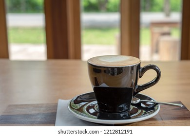Close up a cup of hot cappuccino coffee on wood table