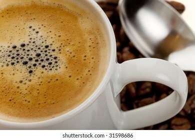 Close up of a cup of hot coffee with beans and spoon in background