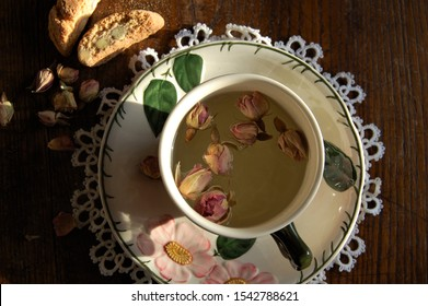 close up of a cup and plate with roses and green leaves decoration and some dry roses  and hot water inside laying on old wooden table and some almond biscuits aside in a warm natural light