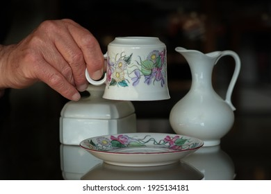 Close up of cup, porcelains and human hand on dark background.