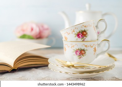 Close up of cup of tea with book, teapot and rose flowers on blue background with vintage tone - Afternoon tea party concept