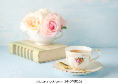 Close up of cup of tea with flowers and book on blue background with vintage tone - Afternoon tea party concept