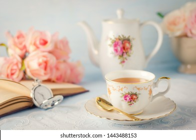 Close up of cup of tea with teapot, rose flowers, pocket watch and book on blue background with vintage tone - Afternoon tea party concept