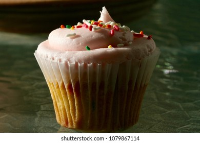 Close up of cupcake with pink icing and colored sprinkles.