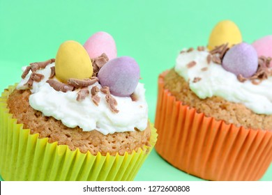 Close up of cupcakes with chocolate eggs on green background