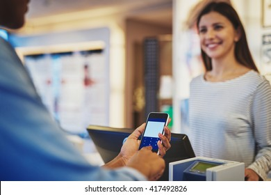 Close up of customer entering information on phone as female cashier smiles in store