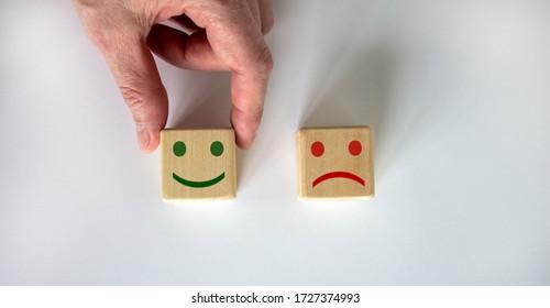 Schließen Sie die Hand des Kunden wählen Sie Lächeln Gesicht Ikone auf Holz Würfel. Service-Bewertung, Zufriedenheitskonzept.