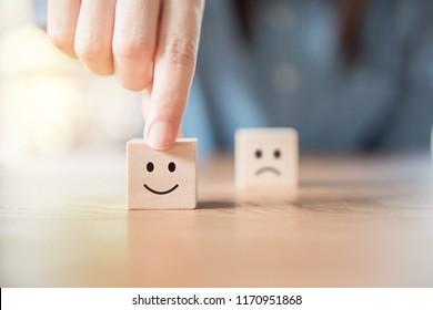Nahaufnahme Kundenhand wählen Sie Smiley Gesicht und unscharfes Gesicht Symbol auf Holz Würfel, Service-Bewertung, Zufriedenheit Konzept.