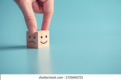 Close up customer hand choose smiley face and sad face icon on wood cube, Service rating, satisfaction concept, copy space.