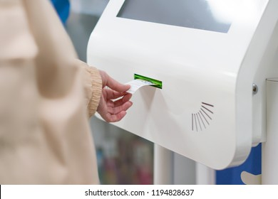 close up customer hand pull a ticket number from dispenser machine to wait in queue in post office