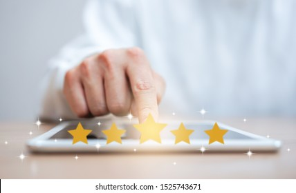 close up customer man hand press on digital tablet screen with gold five star rating feedback icon and press level three rank(good) for give score point to review the service , business concept