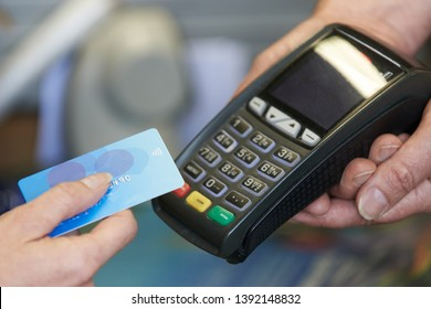 Close Up Of Customer In Shop Making Purchase Using Contactless Payment