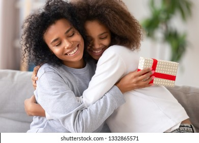 Close up cute african teen daughter congratulate mom with mother day, relative people embracing, mom feels gratitude. Celebration of anniversary or birthday, family life events and best wishes concept
