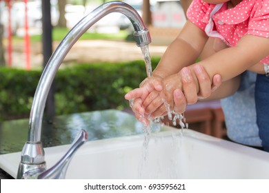 Close up is cute baby little hands with mother help clean washing hand water on the park background.